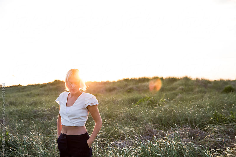 Woman standing in a field with the sun rising behind by Ann-Sophie Fjelloe-Jensen for Stocksy United
