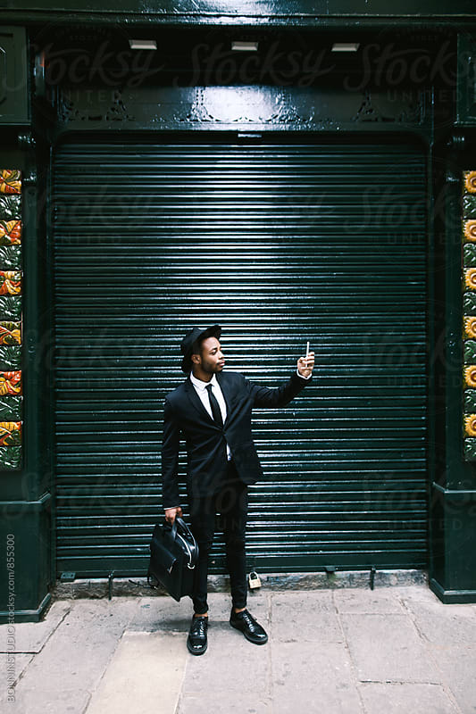Elegant businessman taking photo on the street. by BONNINSTUDIO for Stocksy United
