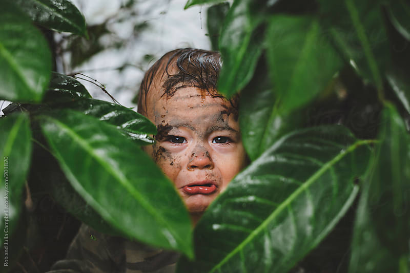 Cute, sad toddler boy crying in the bushes with face covered in mud - funny by Rob and Julia Campbell for Stocksy United