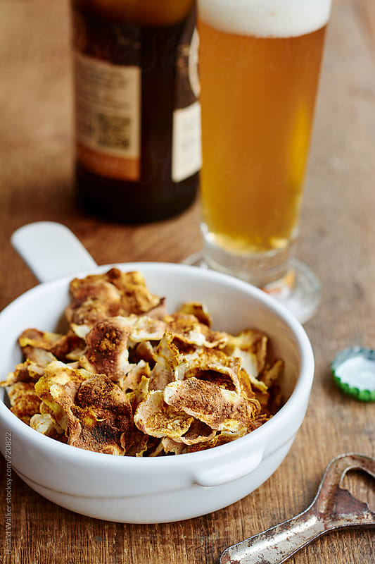 Turnip chips and beer by Harald Walker for Stocksy United