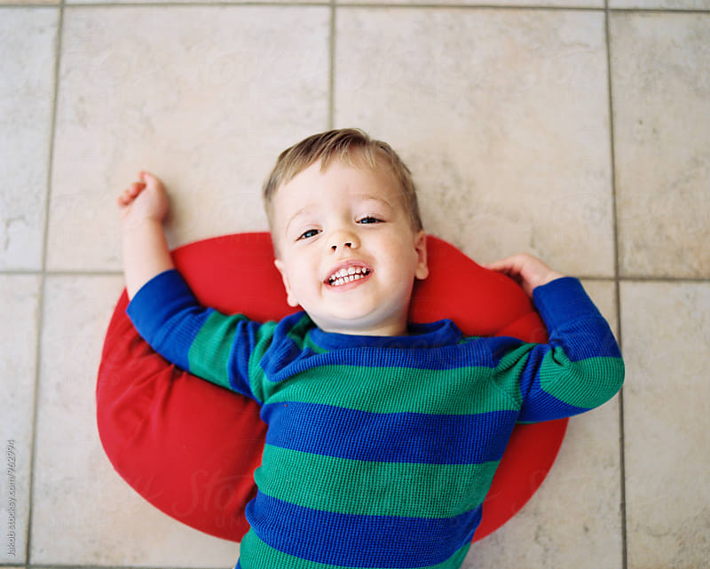 Cute boy toddler laying on the floor with a red pillow underneath him by Jakob for Stocksy United