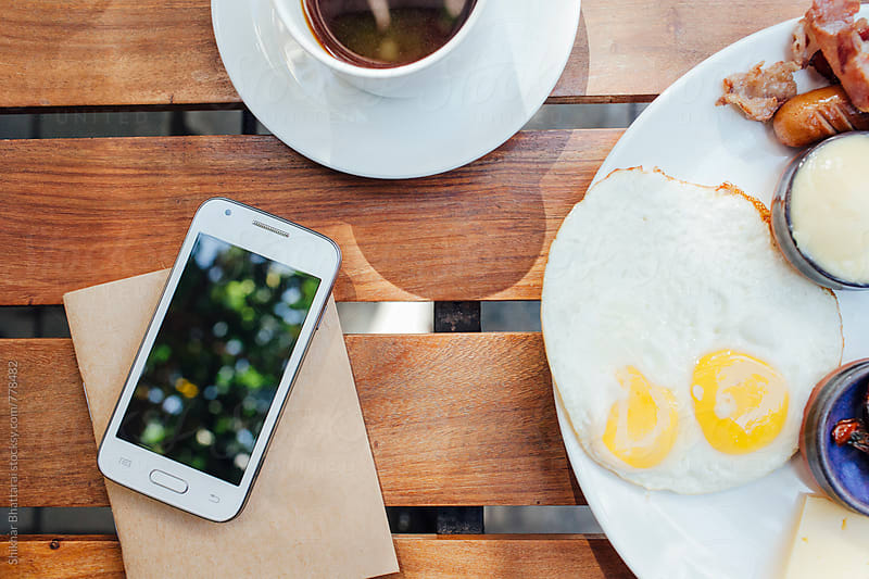 Blank cell phone on top of a notebook with breakfast on the side. by Shikhar Bhattarai for Stocksy United