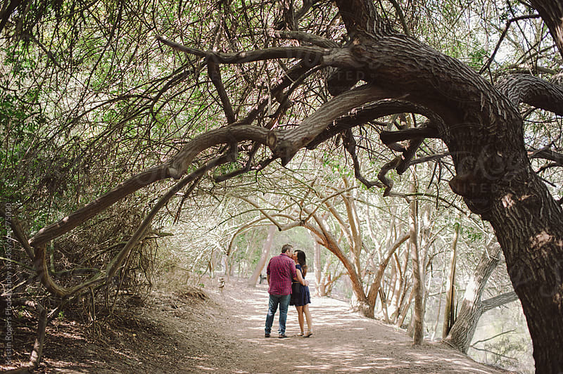 Engaged couple walking and holding hands under trees by Kristin Rogers Photography for Stocksy United