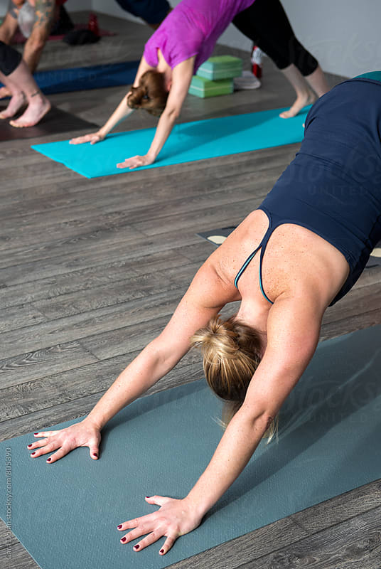 Yoga class in down dog positon by Cara Dolan for Stocksy United