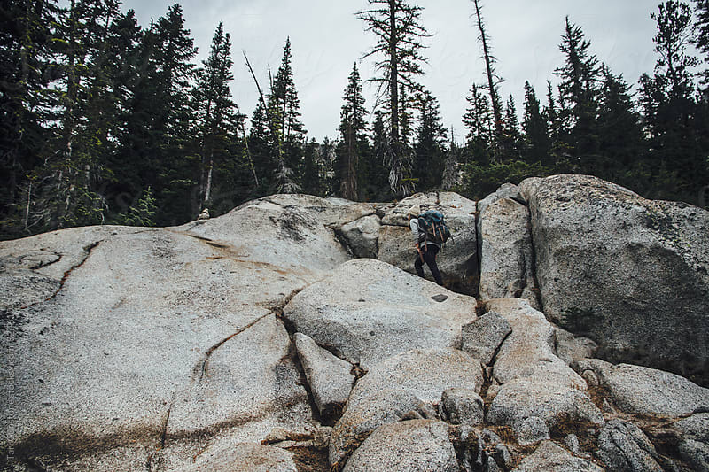 Hiker climbs along granite boulders by Tari Gunstone for Stocksy United