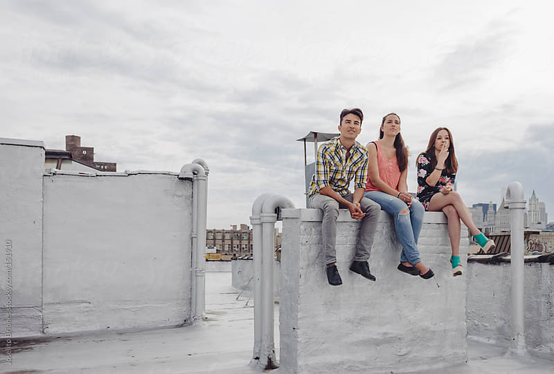 Friends Smoking Cigarettes on a New York Rooftop by Joselito Briones for Stocksy United