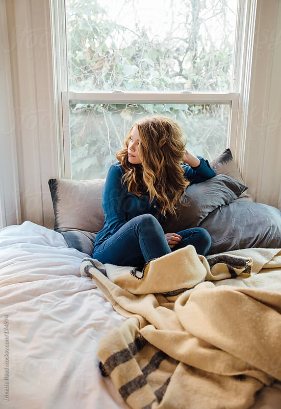 Portrait of woman relaxing on bed by Trinette Reed for Stocksy United