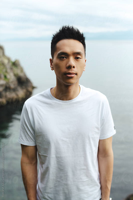 Portrait of young asian man standing near ocean water by Rob and Julia Campbell for Stocksy United