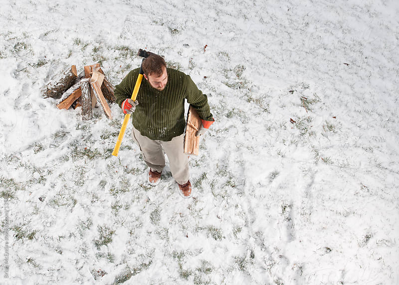 Splitting Firewood: Man Chops Wood For Fire As Snow Falls by Brian McEntire for Stocksy United
