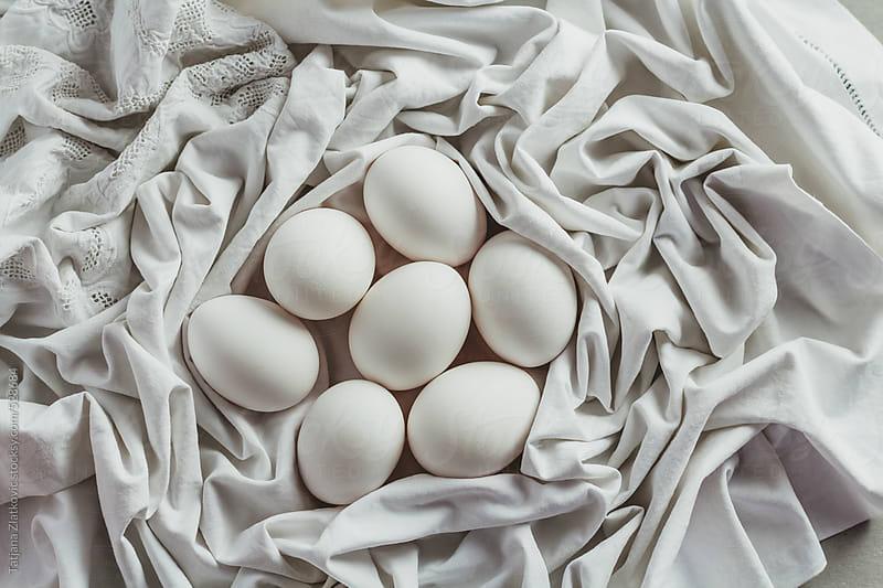 Eggs in tablecloth nest by Tatjana Zlatkovic for Stocksy United