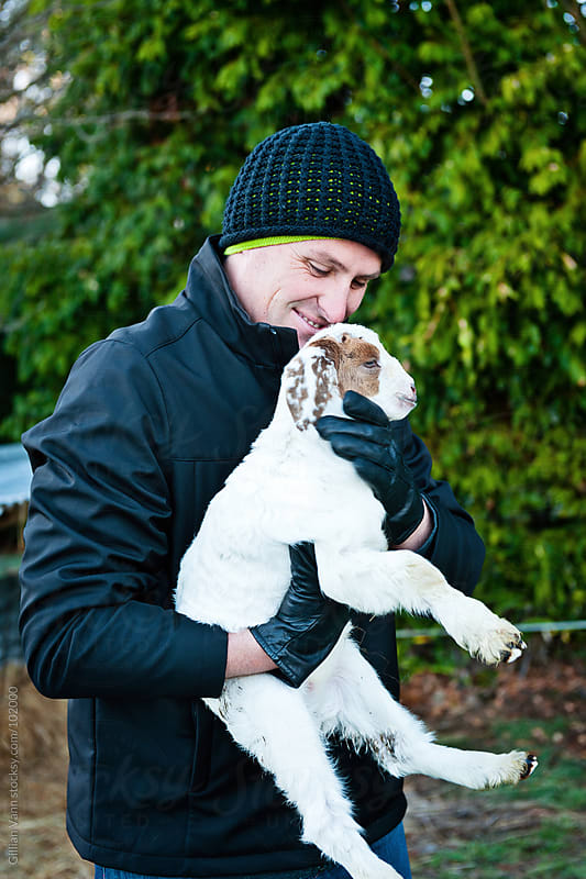 a man holds a pet goat by Gillian Vann for Stocksy United