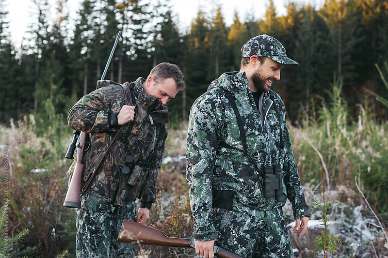 Two men enjoying hunting together by Rob and Julia Campbell for Stocksy United