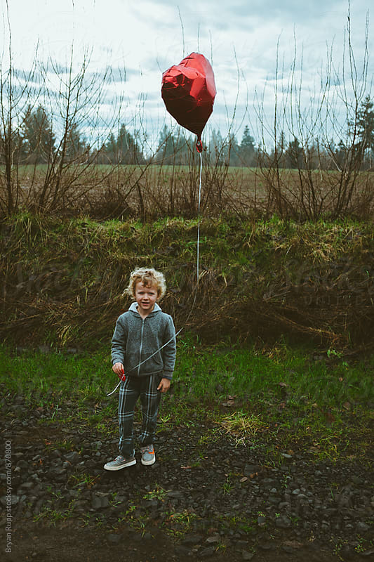 Little Boy Standing Holding Balloon by Bryan Rupp for Stocksy United