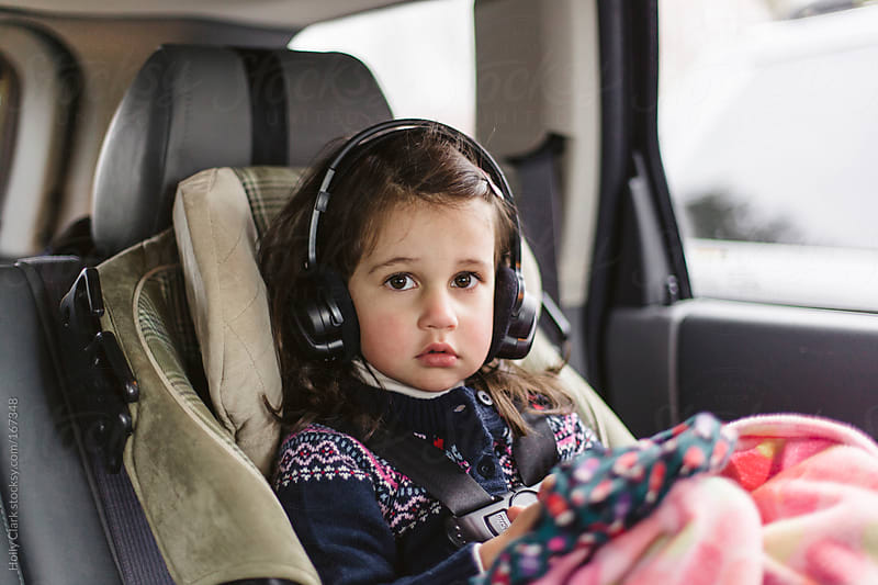 A young child wears headphones in the back of a car. by Holly Clark for Stocksy United