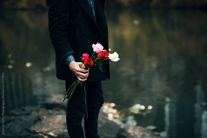 Man's holding roses by Isaiah & Taylor Photography for Stocksy United