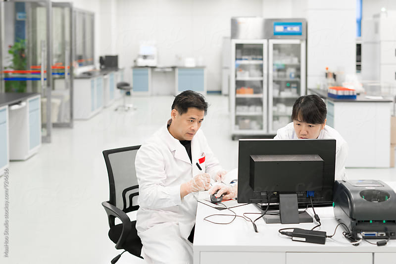 Scientists working on computers in lab by Maa Hoo for Stocksy United