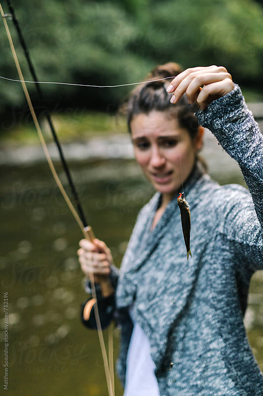 Woman holding very small fish on end of fishing line with disappointed expression by Matthew Spaulding for Stocksy United