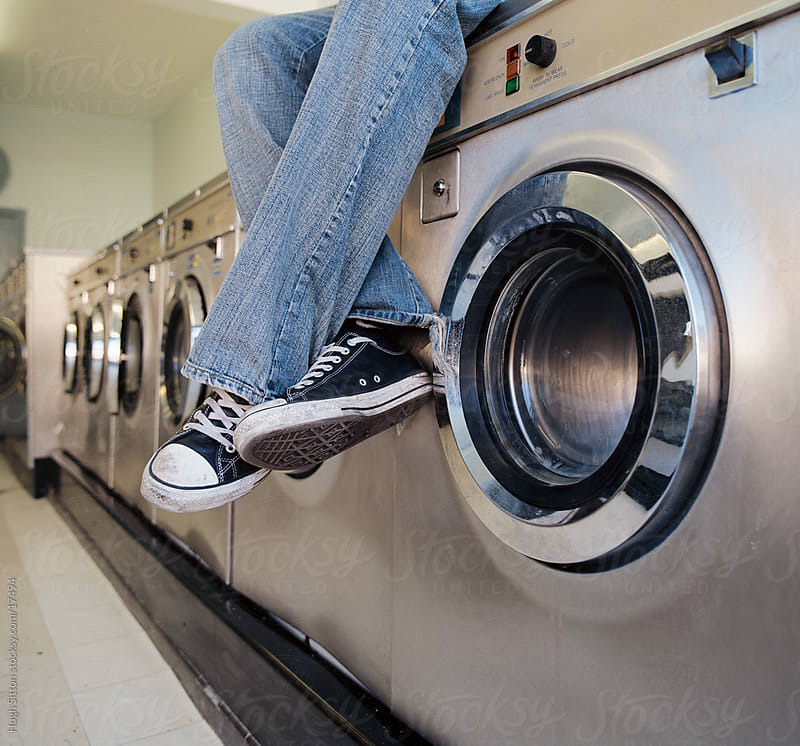 Man sitting on washing machine. by Hugh Sitton for Stocksy United