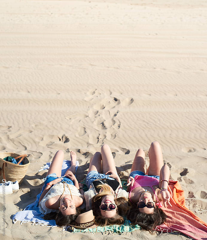 Three girls on beach blanket by Guille Faingold for Stocksy United
