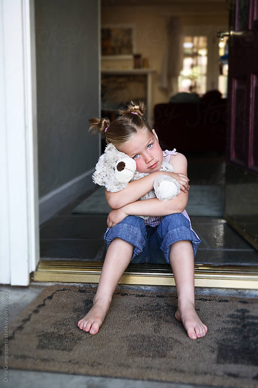 Girl with hair up in two buns holding stuffed bear while sitting in doorway by Dina Giangregorio for Stocksy United