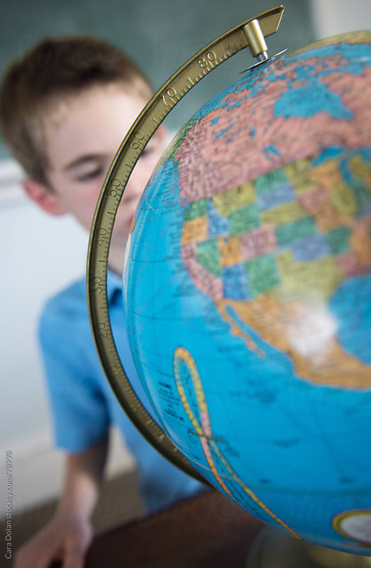 Boy in classroom looks at countries on a globe by Cara Dolan for Stocksy United