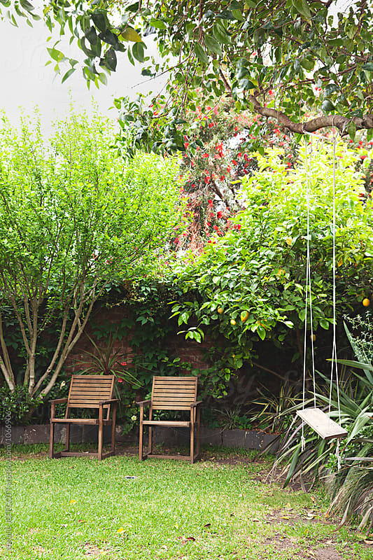 Backyard garden with two chairs and a swing by Natalie JEFFCOTT for Stocksy United