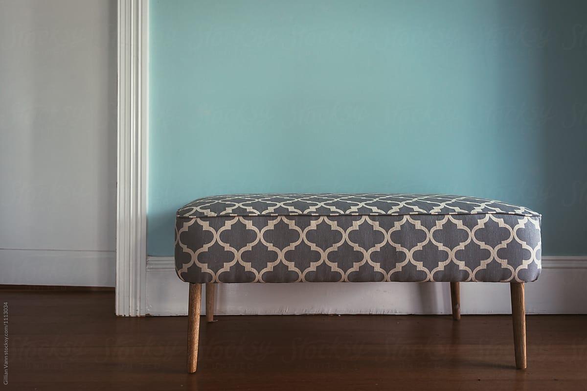 modern ottoman bench against a blue