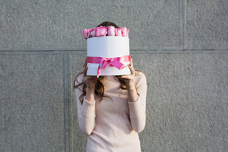 Young woman hides her face with box full of pink roses by Jovana Rikalo for Stocksy United