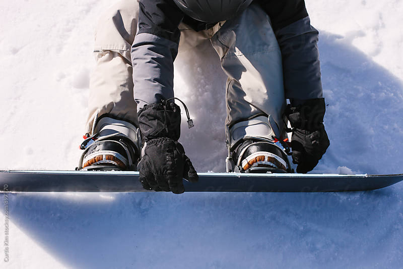 Young snowboarder strapping on his snowboard by Curtis Kim for Stocksy United