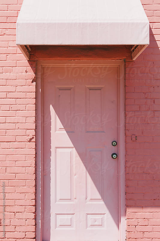 Pink door with awning on a sunny day by Amanda Worrall for Stocksy United
