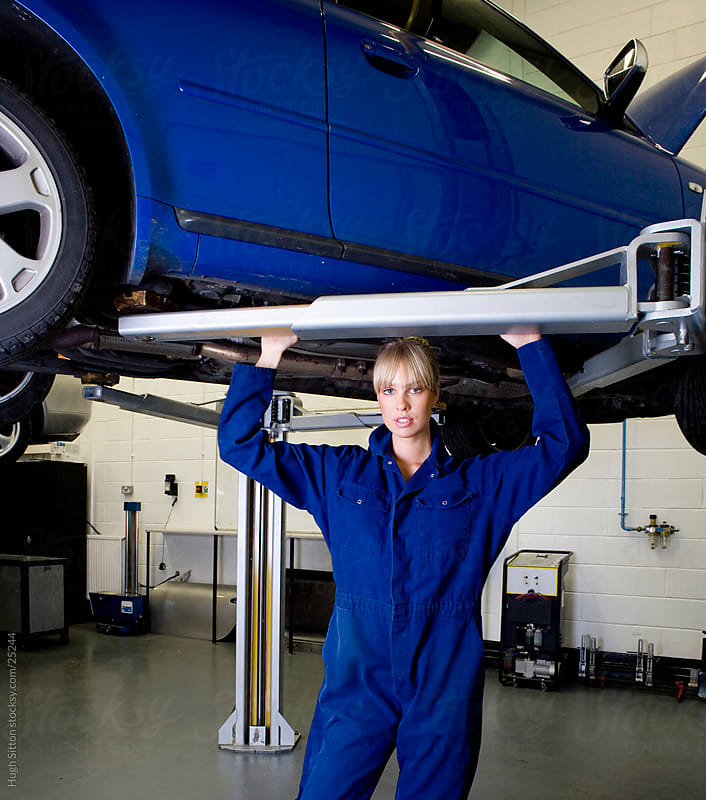 Female car mechanic working in busy garage. by Hugh Sitton for Stocksy United