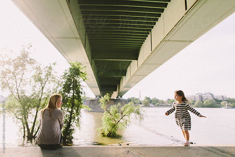 Mother and her little daughter under the bridge by Evgenij Yulkin for Stocksy United