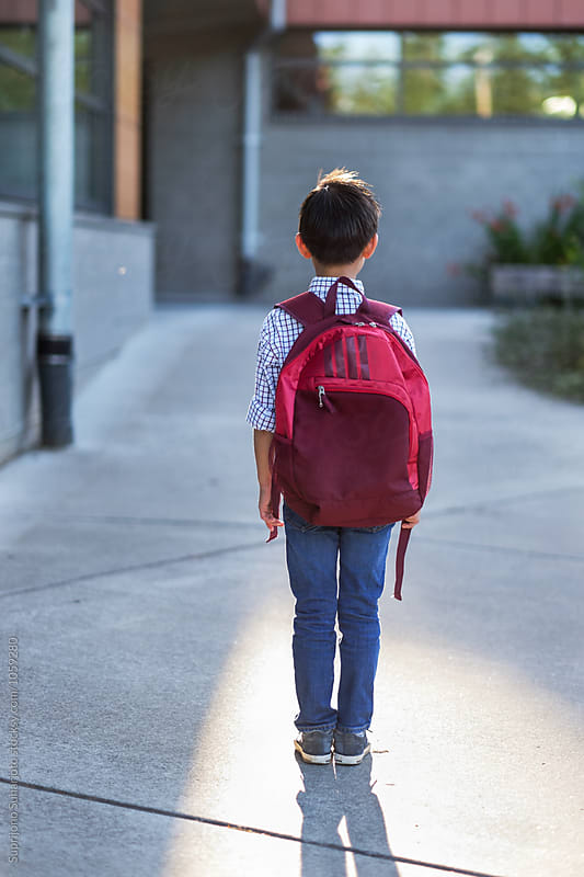 Back to school: Asian kid carrying a backpack in school by Suprijono Suharjoto for Stocksy United