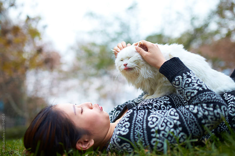 young woman with her cat outdoor by cuiyan Liu for Stocksy United