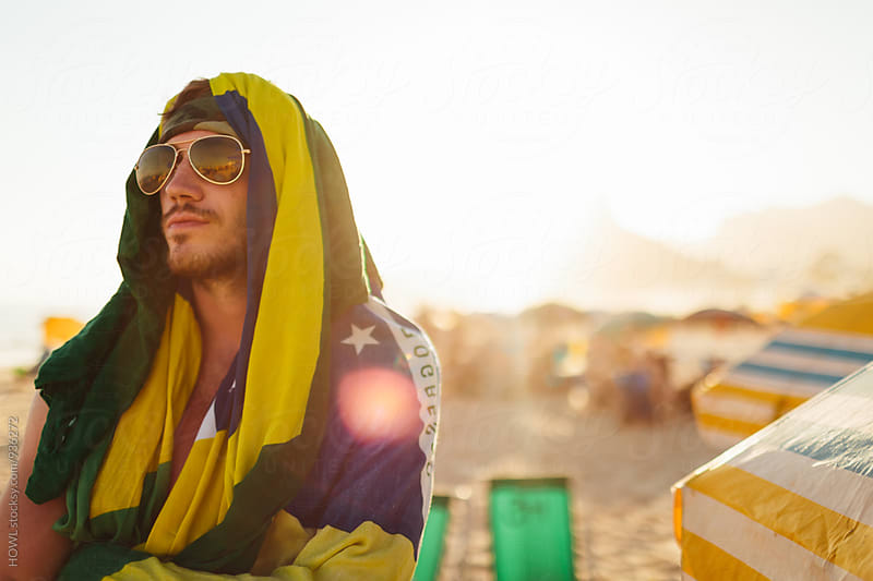 Young scruffy man in sunglasses stands stoic at the beach  by HOWL for Stocksy United