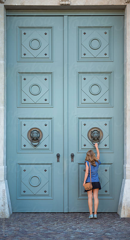 Small woman in front of a big antique door by RG&B Images for Stocksy United