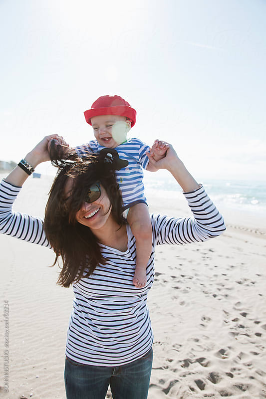 Mom with her baby smiling on the beach by BONNINSTUDIO for Stocksy United
