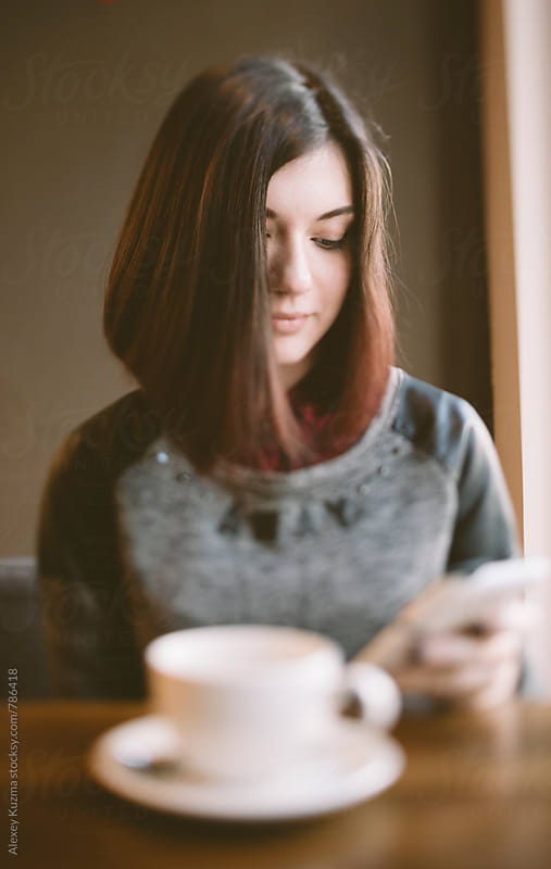 young woman sitting in a coffee shop by Vesna for Stocksy United