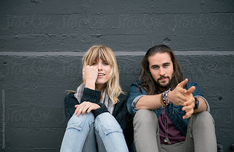 Young attractive couple sitting against wall and looking at camera by Emmanuel Hidalgo for Stocksy United