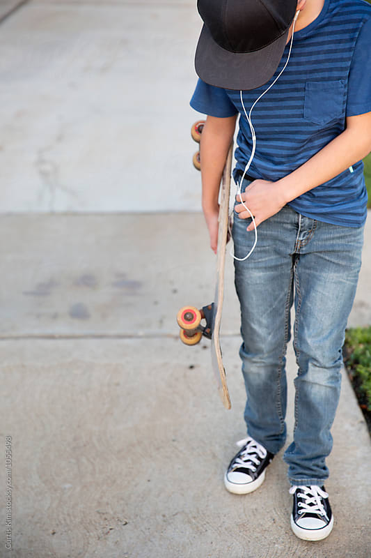 Boy listening to music and holding his skateboard by Curtis Kim for Stocksy United