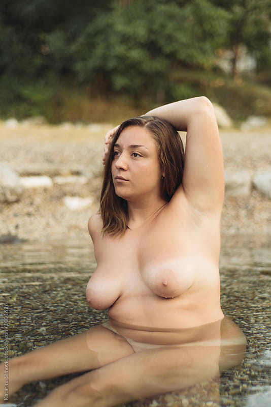 Portrait of naked woman sitting in water by Katarina Simovic for Stocksy United