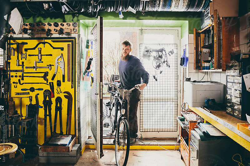 Young mechanic bringing bicycle into workshop by Lior + Lone for Stocksy United