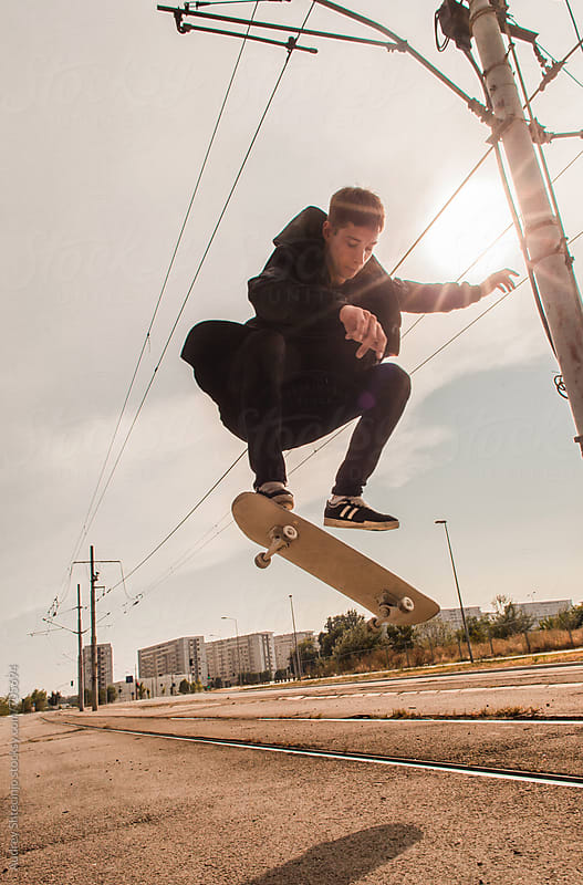 Young skateboarder doing tricks on street during sunny day, by Marko Milanovic for Stocksy United