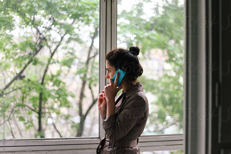 Brunette woman talking on the phone, looking through the window by Marija Kovac for Stocksy United