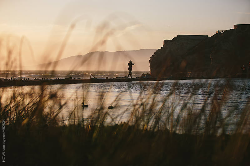 Young woman walking alone the California coast at sunset in San Francisco  by HOWL for Stocksy United