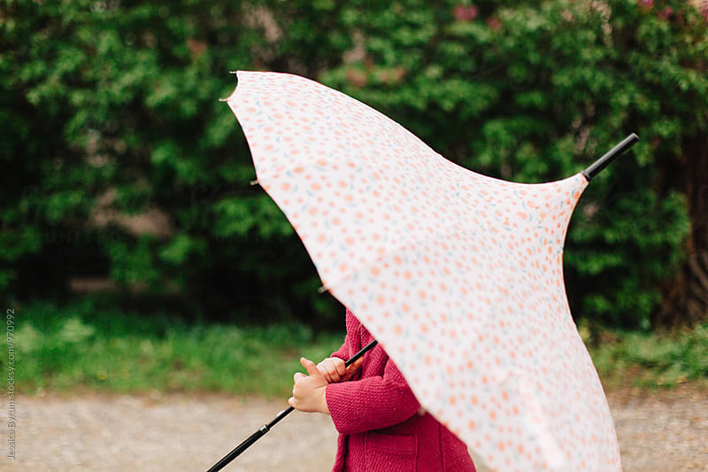 Toddler girl in a pink jacket and rain boots outside with an umbrella. by Jessica Byrum for Stocksy United