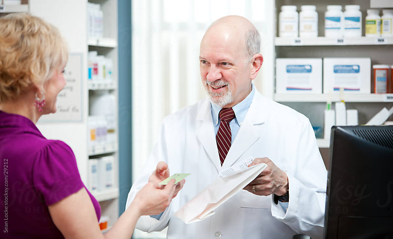 Pharmacy: Customer Checks Out with Pharmacist by Sean Locke for Stocksy United