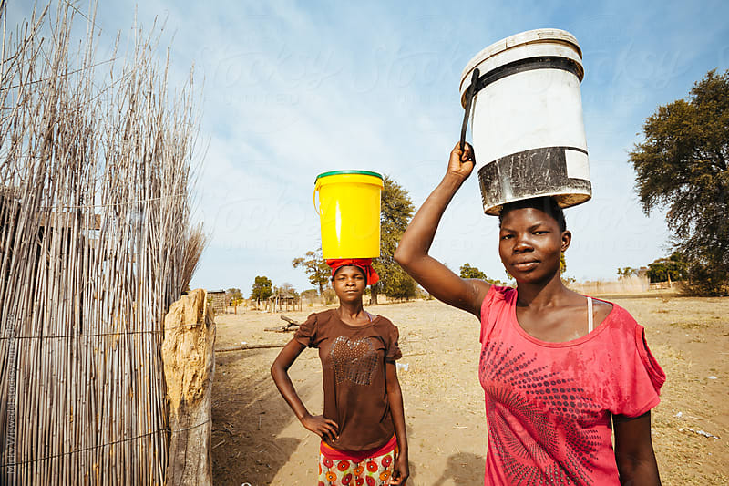 Young African Hambukushu women carrying water by Micky Wiswedel for Stocksy United