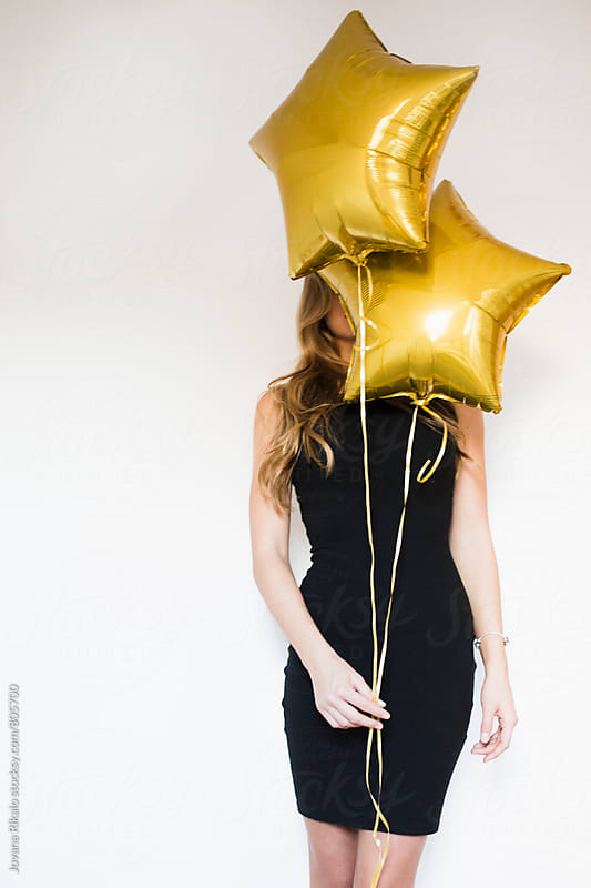 Young woman holding balloons in front of her face by Jovana Rikalo for Stocksy United