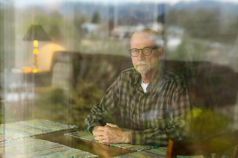 Senior man seen through a window  by David Smart for Stocksy United